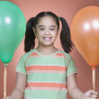 Portrait of young girl holding balloons — Stock Photo