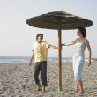 Foto Stock: Young couple laughing underneath umbrellon beach