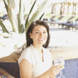 Stock Photo: Hispanic woman with drink at hotel bar