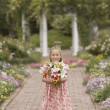 Girl holding flowers in garden - Stock Photo