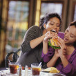Young women fighting to take bite of hamburger — Stock Photo #13232267