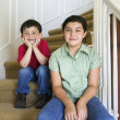 Portrait of brother and sister sitting on stairs - Stock Photo