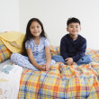Brother and sister sitting on bed together — Stock Photo