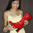 Portrait of woman holding red boot - Stock Photo