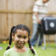 African girl with father barbequing in background - Stock Photo