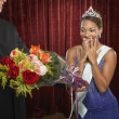 Beauty queen gasping and receiving flowers — Stock Photo