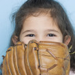Portrait of girl with baseball mitt covering mouth — Stock Photo