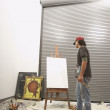 Stock Photo: Male artist considering blank easel