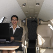 Businesswoman working on laptop inside airplane — Stock Photo