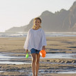 Portrait of girl walking on beach with bucket and shovel - Stock Photo