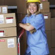Female warehouse worker with hard hat — Stockfoto