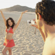 Man taking photograph of woman on the beach — Stock Photo #13232445