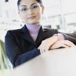 Asian businesswoman leaning on counter  — Stock Photo