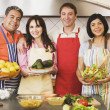 Two middle-aged couple wearing aprons - Stock Photo