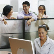 Asian businesspeople pointing at businesswoman — Stock Photo
