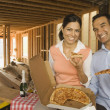 Stock Photo: Hispanic couple having pizza and champagne at construction site