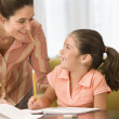 Mother helping daughter with homework — Stock Photo #13232494