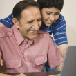 Hispanic grandfather and grandson using laptop - Stock Photo