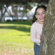 Young girl hiding behind a tree — Stock Photo #13232516