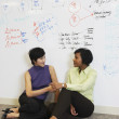 Two businesswomen sitting on floor in front of whiteboard wall — Stok fotoğraf