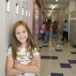 Young girl smiling in school hallway — Stock Photo #13232584