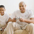 Stock Photo: Indifather and son playing video games