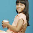 Young girl holding glass of milk - Stock Photo