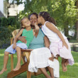 African mother and young daughters hugging outdoors - Stock Photo