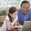 Asian grandfather and granddaughter looking at laptop — Stock Photo