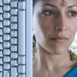 Indian woman wearing bindi next to computer keyboard — Stock Photo
