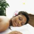 African woman laying on spa table — Stock Photo