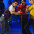 Three young men with cocktails at nightclub table — ストック写真