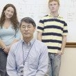 Male teacher with two students - Stock Photo