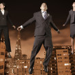 Stock Photo: Businesspeople floating above the city