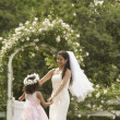 Hispanic bride and young girl dancing in circle — Stock Photo