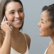 Teenage girl and friend chat on mobile phone — Stock Photo