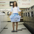 Full view of womwith basket of clothes in laundromat — Stock Photo #13232848