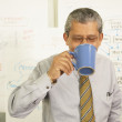 Businessman drinking from coffee cup — Stock Photo