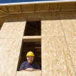 Construction worker looking out of window in unfinished building — Stock Photo #13232850