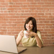 Young woman using a laptop and having a cup of coffee — Stock Photo #13232880