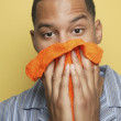 African man in pajamas holding washcloth to face - Stock Photo