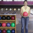 Portrait of woman holding bowling ball - Photo