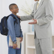 African father seeing son off to school — Stock Photo