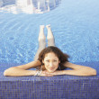 Hispanic woman floating in pool - Stock Photo