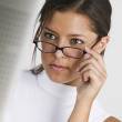 Young woman looking over glasses — Stock Photo