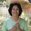 Senior Hispanic woman holding parasol outdoors - Stock Photo