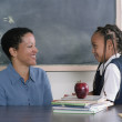 Teacher and school girl talking in classroom — Stock Photo