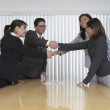 Business professionals shake hands on a deal - Stock Photo