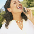 Woman laughing while talking on cell phone — Stock Photo