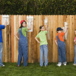 Mixed Race family painting fence — Stock Photo